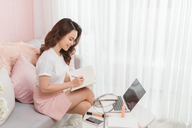 La giovane donna casuale asiatica che lavora alla piccola impresa in linea imballandola controlla l'elemento in un taccuino e che prende le note. concetto di proprietario di piccola impresa vendita online, concetto di e-commerce