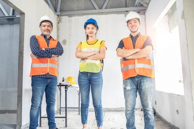 Giovani coppie asiatiche che controllano casa con i clienti della casa della costruzione di ispezione domestica di ingegneria del caposquadra