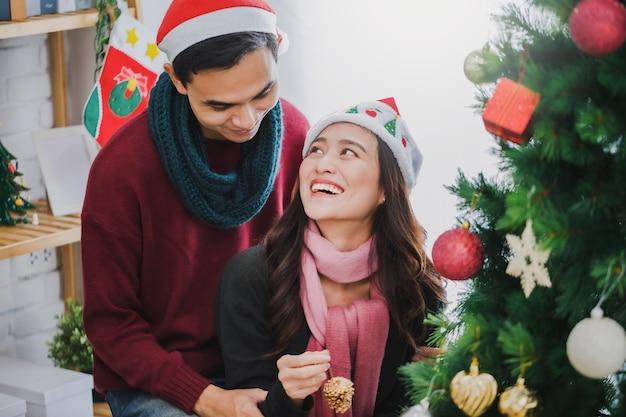 Giovani coppie asiatiche che decorano un albero di natale