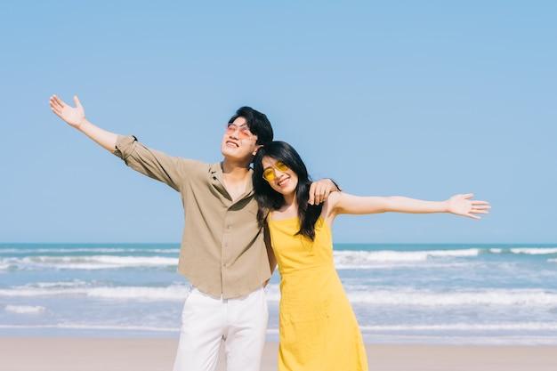 Giovani coppie asiatiche che godono delle vacanze estive sulla spiaggia
