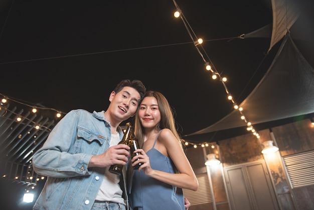 Il giovane amante delle coppie asiatiche si diverte a ballare e bere nella festa di notte sul pavimento del locale notturno sul tetto tenendo la bottiglia di birra e il contatto visivo flirtando