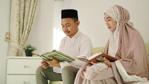 Giovani coppie asiatiche che leggono insieme il corano