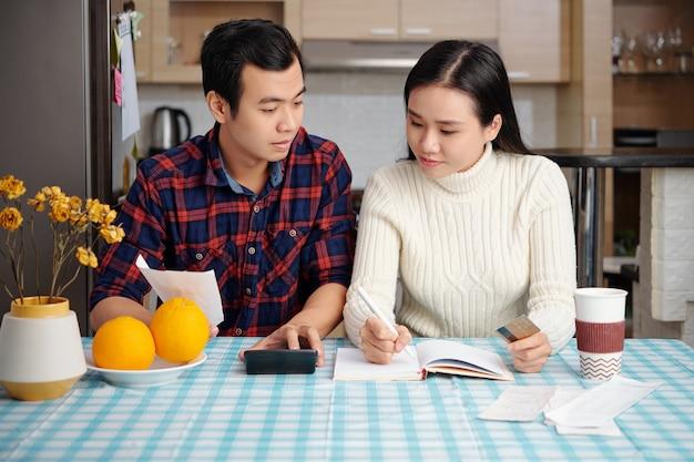 Giovane coppia asiatica che esamina le bollette, pianifica il budget familiare e calcola le finanze al tavolo della cucina con bollette, calcolatrice e pianificatore
