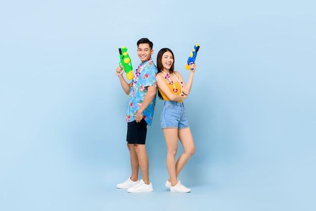 Giovani coppie asiatiche in abiti estivi con pistole ad acqua per il festival songkran in thailandia e sud-est asiatico