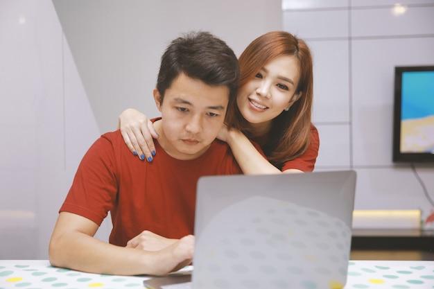 Giovani coppie asiatiche che usano il computer portatile sulla scrivania a casa con sfondo bianco interno domestico