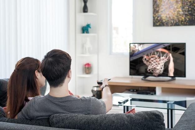 Gioco di sport di pallacanestro di sorveglianza delle giovani coppie asiatiche sulla tv a casa.