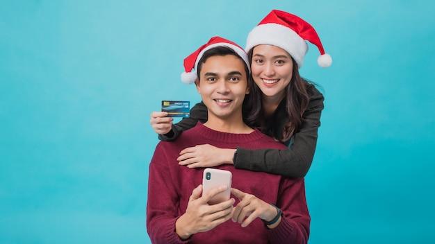 Giovani coppie asiatiche che indossano cappelli di babbo natale e shopping online con carta di credito e smartphone