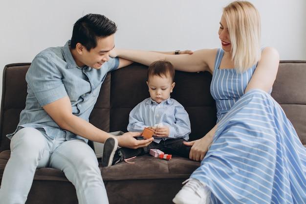 Il giovane papà asiatico e la mamma bionda caucasica giocano la seduta con suo figlio nella stanza luminosa