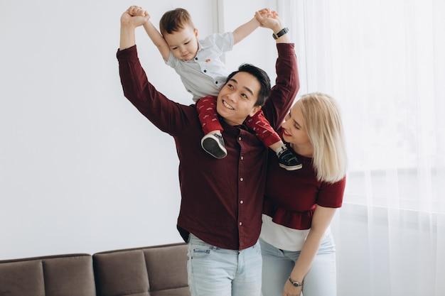 Il giovane papà asiatico e la mamma bionda europea tengono il figlio in sue braccia nella stanza luminosa. concetto multiculturale di tendenza