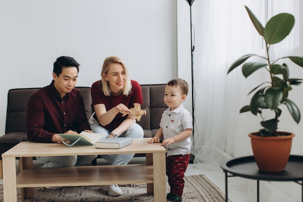 Il giovane papà asiatico e la mamma bionda europea giocano la seduta con suo figlio nella stanza luminosa