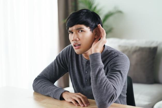 Il giovane uomo asiatico sordo disabile che ha problemi di udito tiene la mano sull'orecchio, ascolta attentamente, con problemi di udito.
