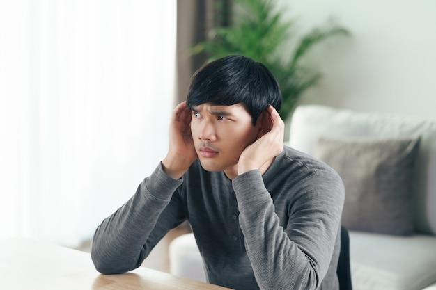Il giovane asiatico disabile sordo con problemi di udito tiene la mano sull'orecchio, ascolta attentamente, con problemi di udito.