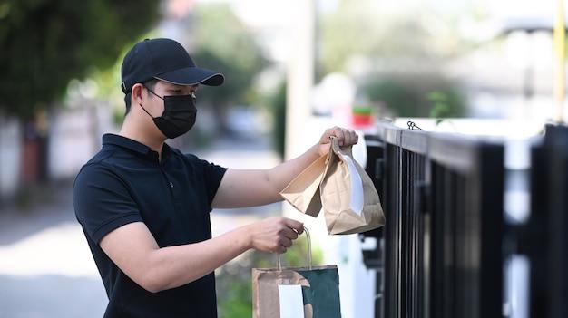Giovane fattorino asiatico con maschera protettiva che tiene in mano un sacchetto di carta con cibo e aspetta il cliente alla porta di casa.