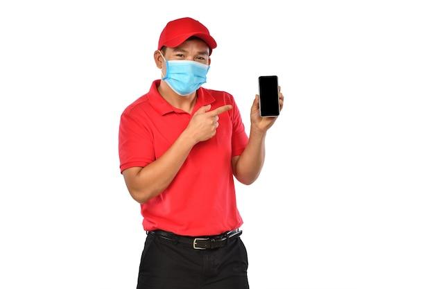 Giovane fattorino asiatico in uniforme rossa, mascherina medica, guanti protettivi che tengono e introducono l'uso del telefono astuto