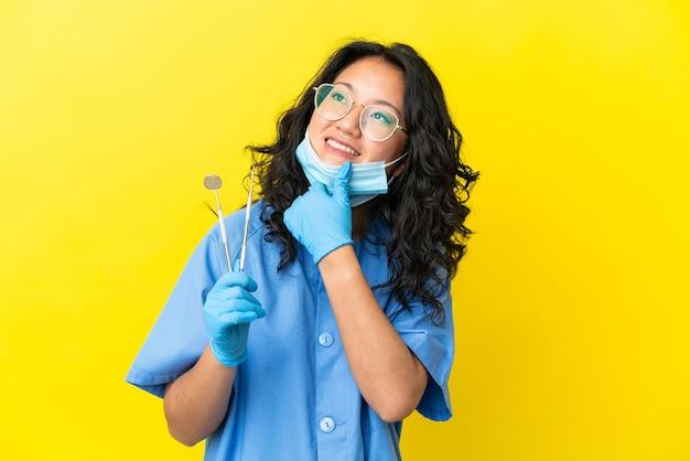 Giovane dentista asiatico che tiene gli strumenti su sfondo isolato guardando di lato e sorridente