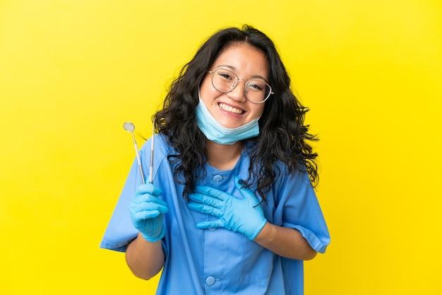 Giovane dentista asiatico che tiene gli strumenti su sfondo isolato sorridendo molto