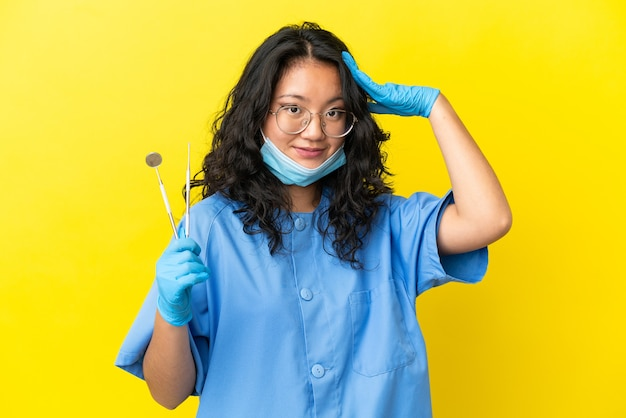 Giovane dentista asiatico che tiene gli strumenti su sfondo isolato con espressione di sorpresa