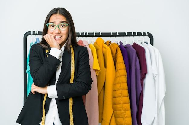 Giovane donna asiatica del progettista isolata sulle unghie mordaci della parete bianca, nervosa e molto ansiosa.