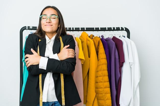 La giovane donna asiatica del progettista isolata sul muro bianco abbraccia, sorridendo spensierata e felice.