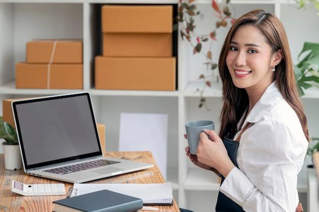 Giovane imprenditrice asiatica che tiene in mano una tazza, sorride e guarda la telecamera mentre lavora con la sua piccola impresa a casa.