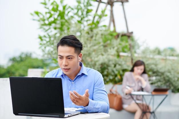 Giovane imprenditore asiatico seduto al tavolo in caffè all'aperto e videochiamata collega o partner commerciale
