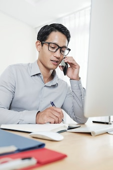 Giovane imprenditore asiatico parlando al telefono con un partner commerciale e scrivendo nel pianificatore