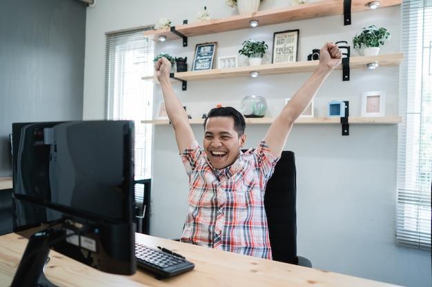Giovane asiatica eccitata mentre si lavora in ufficio