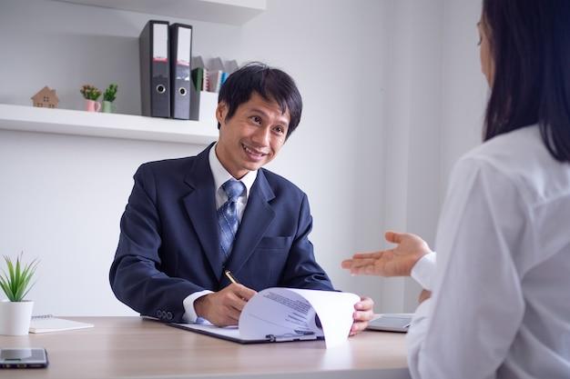 I giovani dirigenti asiatici hanno intervistato i candidati di buon umore. il capo parla e chiede la passata esperienza lavorativa del candidato. attitudine a rispondere alle domande durante il colloquio