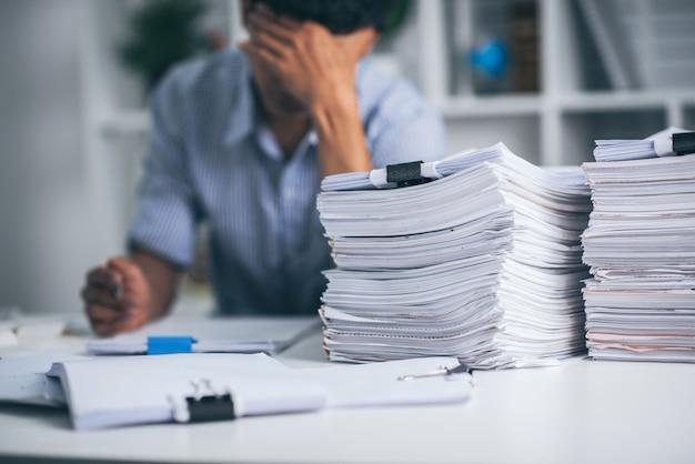 Giovane uomo d'affari asiatico esaurito con scrivania disordinata e pila di carte, lavorando occupato, superlavoro.