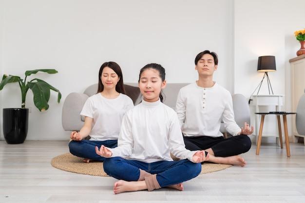 Giovane famiglia asiatica facendo esercizio insieme a casa