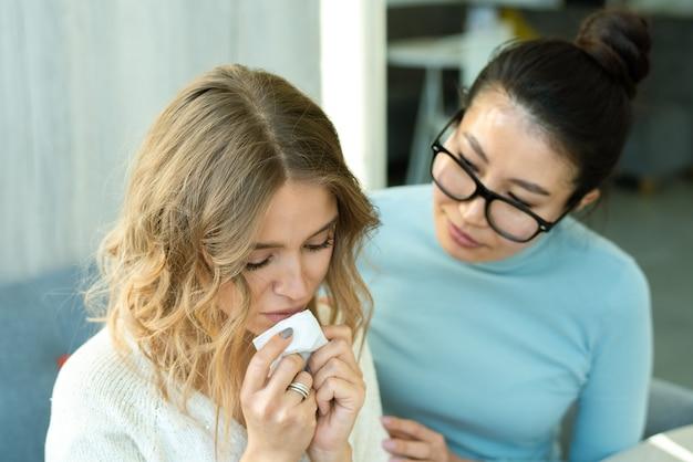 Giovane femmina asiatica in occhiali confortante il suo amico sconvolto con il fazzoletto mentre è seduto nella caffetteria