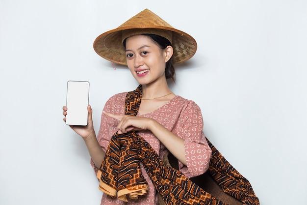 Giovane agricoltore femminile asiatico che dimostra telefono cellulare su sfondo bianco