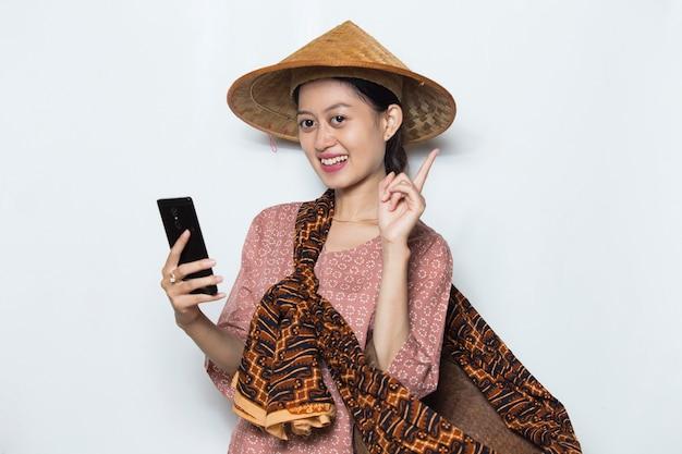 Giovane agricoltore femminile asiatico che per mezzo del telefono cellulare su fondo bianco