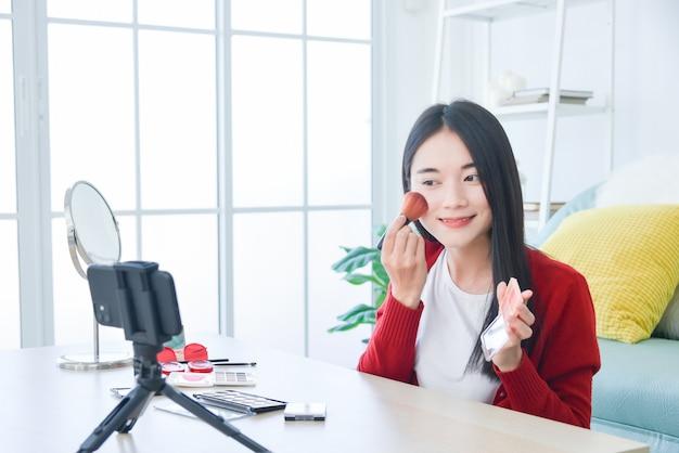 Giovane truccatrice asiatica, vlogger di bellezza o blogger che registra un tutorial di trucco cosmetico vlog