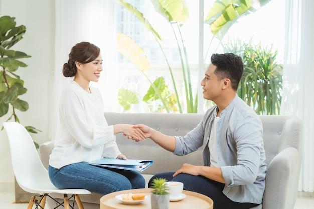 Giovane psicologo femminile asiatico che si consulta con il suo cliente nel suo ufficio.