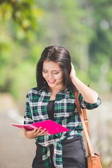 La giovane tenuta asiatica della studentessa prenota mentre cammina sul parco