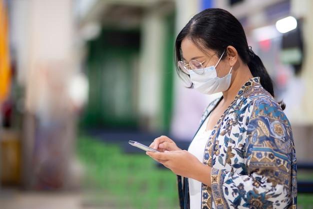 Giovani turiste asiatiche con gli occhiali vestiti in stile casual, indossa una maschera protettiva, usa il tuo smartphone in giro per la biglietteria alla stazione dei treni