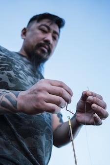 Giovane pescatore asiatico che prepara il gancio