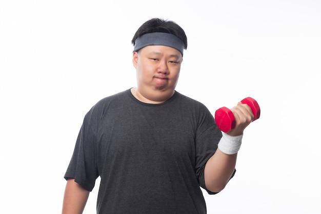 Giovane esercizio grasso asiatico divertente dell'uomo di sport con la testa di legno isolata