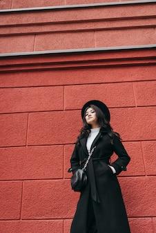 Giovane ragazza asiatica in cappotto scuro e cappello in piedi davanti al muro rosso, ritratto a piedi d'autunno