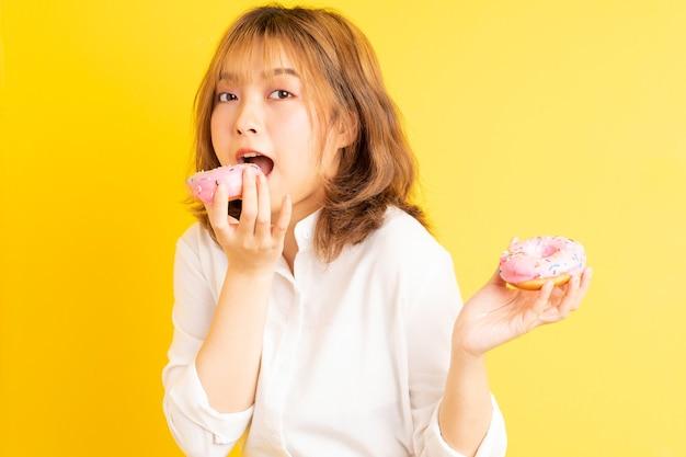 Giovane ragazza asiatica che tiene la ciambella con l'espressione allegra sullo sfondo