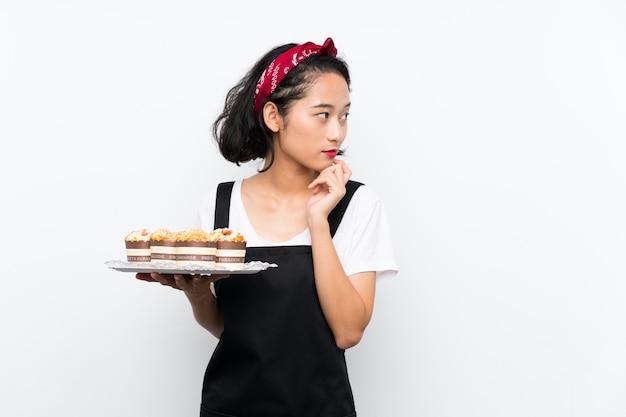 La giovane ragazza asiatica che tiene i lotti del muffin agglutina sopra fondo bianco isolato che pensa un'idea e che guarda il lato