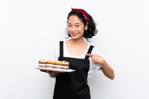 La giovane ragazza asiatica che tiene i lotti del muffin agglutina sopra fondo bianco isolato con espressione facciale di sorpresa