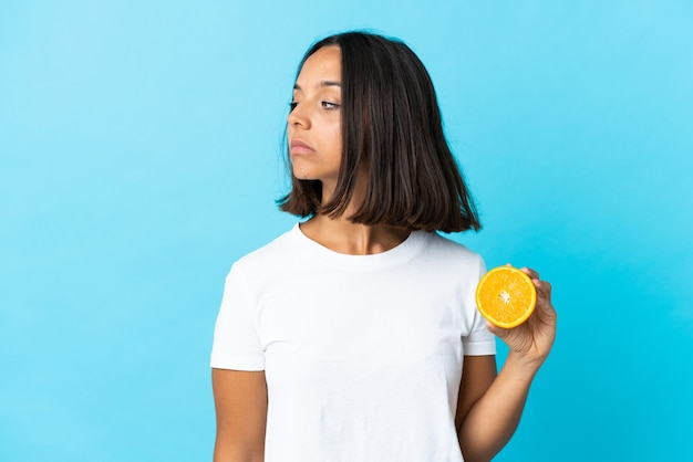 Giovane ragazza asiatica che tiene un'arancia isolata sull'azzurro che osserva al lato