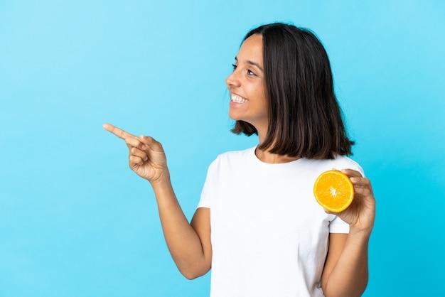 Giovane ragazza asiatica che tiene un arancio isolato sul dito puntato blu al lato
