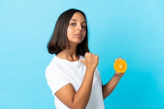 Giovane ragazza asiatica che tiene un'arancia isolata sull'azzurro orgoglioso e soddisfatto di sé