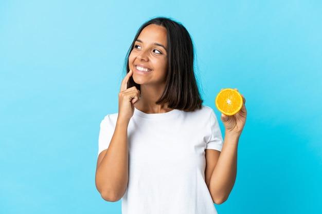 Giovane ragazza asiatica che tiene un'arancia isolata sull'azzurro che pensa un'idea mentre osserva in su