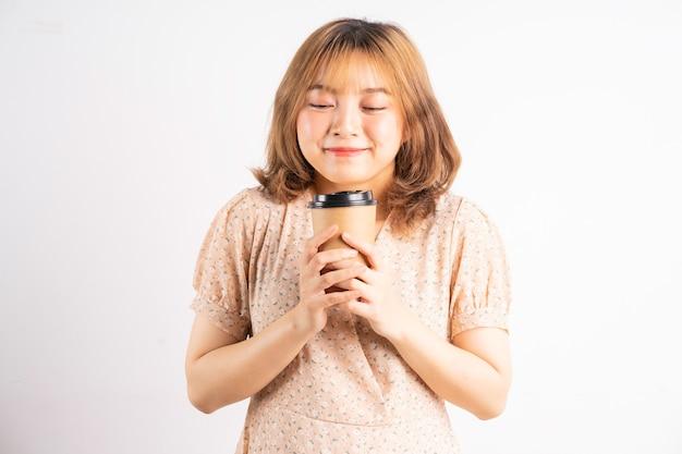 Giovane ragazza asiatica che tiene telefono con espressioni e gesti su bianco