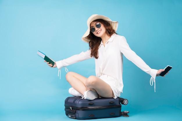 Giovane ragazza asiatica che tiene biglietto aereo e telefono che si siedono sulla valigia