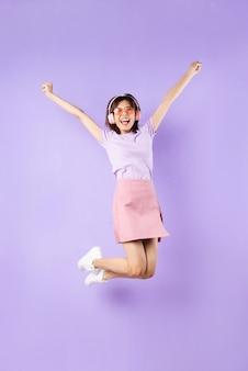 Giovane ragazza asiatica che salta su sfondo viola